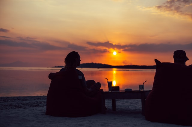 Silhouettes of two people on a beach drinking cocktails and watching the sunsetting